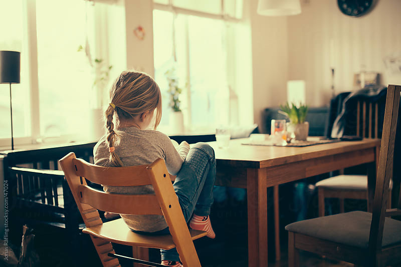 Young girl sitting lonely at the kitchen table by Jonas Räfling for Stocksy United