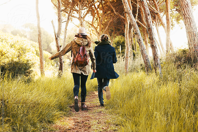 Back view of a hipster couple running in the forest. by BONNINSTUDIO for Stocksy United