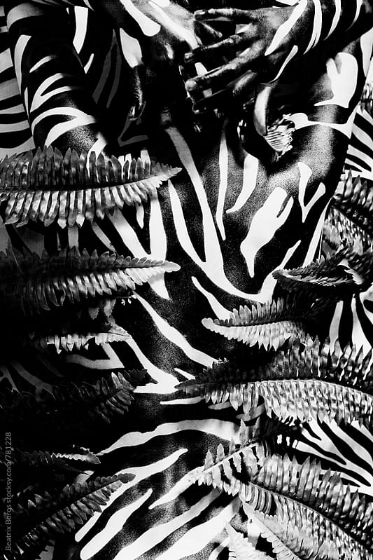 Zebra stripes on woman's back among the plants by Beatrix Boros for Stocksy United