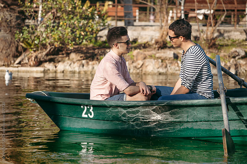 Happy gay couple rowing boat on a lake. by BONNINSTUDIO for Stocksy United
