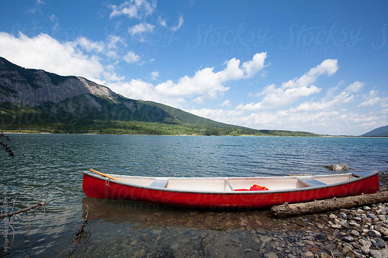 Red boat on a mountain lake in Canada by Mima Foto for Stocksy United
