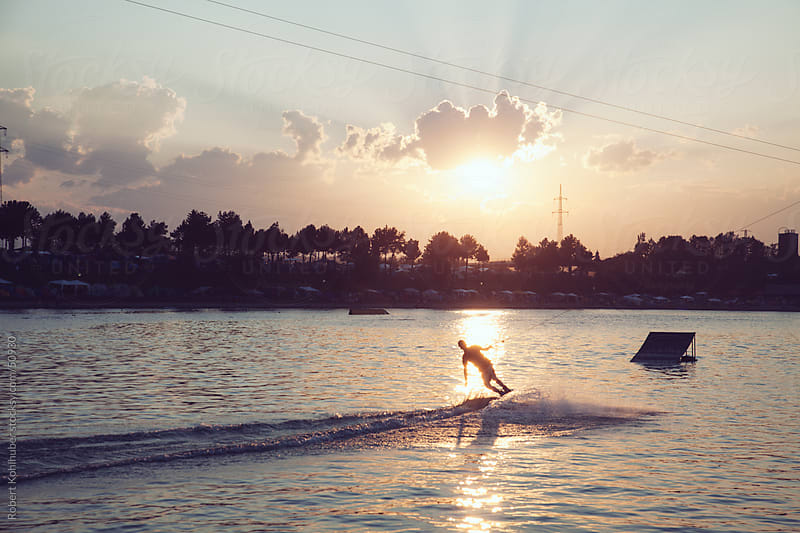 Wakeboarding on a lake at dusk by Robert Kohlhuber for Stocksy United