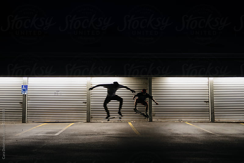 Skateboarders in a parking lot at night by Cara Slifka for Stocksy United