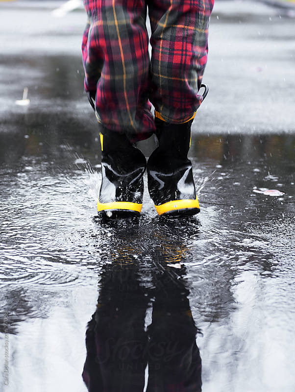 Child wearing rubber boots splashes in a rain puddle  by Cara Dolan for Stocksy United