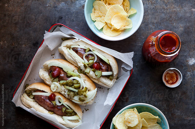 Sausages in bread buns with relish and potato chips by Nadine Greeff for Stocksy United