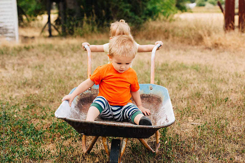 Big sister gives her little brother a ride in a wheelbarrow. by Jessica Byrum for Stocksy United