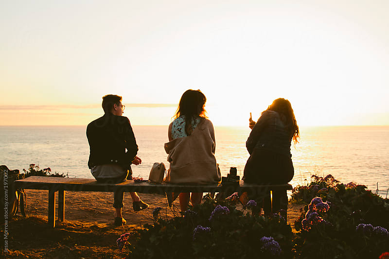 Group sits on bench watching sunset by Jesse Morrow for Stocksy United