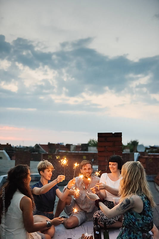 Young people celebrating on a rooftop by VegterFoto for Stocksy United