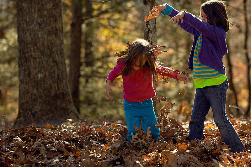 Sisters playing in fall leaves by Alicja Colon for Stocksy United