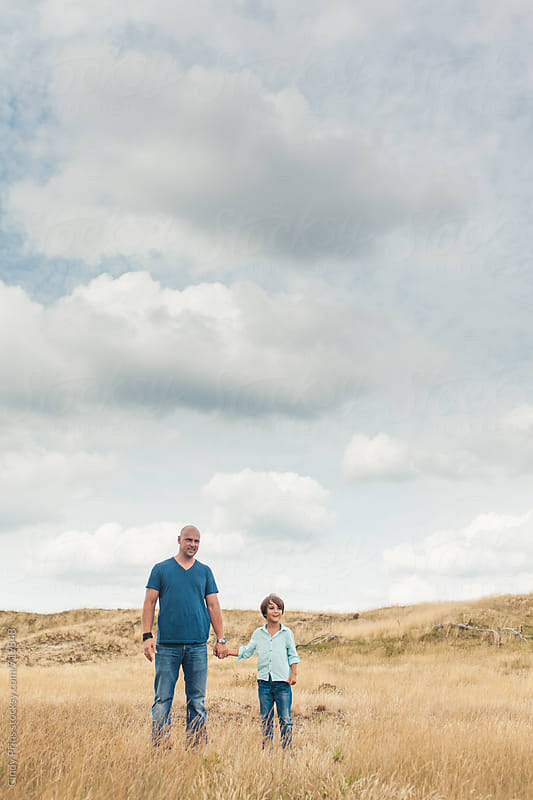 Father and son standing in a golden field against a big sky by Cindy Prins for Stocksy United