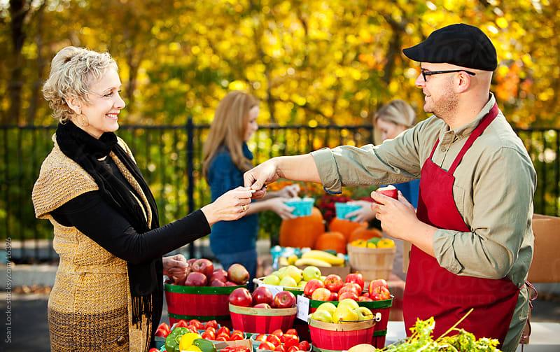 Farmer's Market: Customer Takes Apple Sample from Grower by Sean Locke for Stocksy United