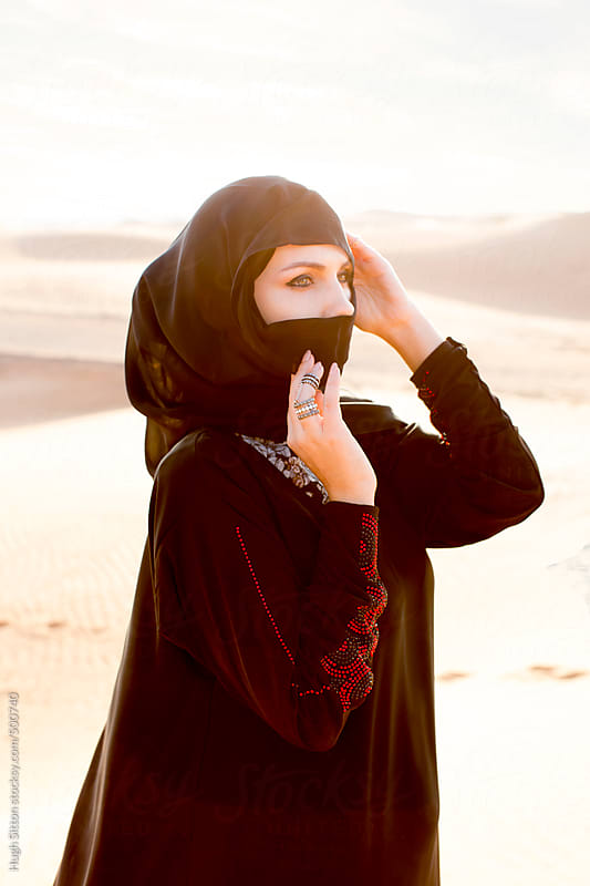 Middle Eastern woman wearing hijab in desert. Dubai. by Hugh Sitton for Stocksy United