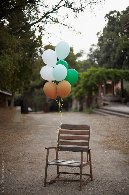 Old chair with attached balloons in a children's party by Miquel Llonch for Stocksy United