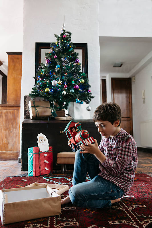 Surprized 7 years old boy with Christmas present in his hand by Beatrix Boros for Stocksy United
