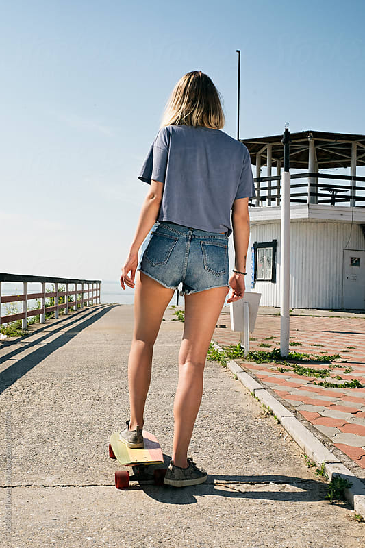 Back view of young girl on longboard by Danil Nevsky for Stocksy United