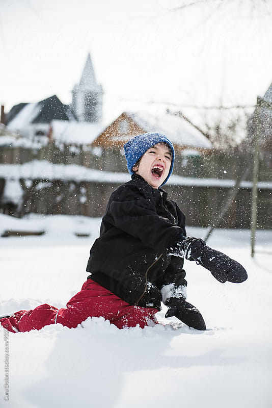 Happy boy throws snow in his back yard by Cara Dolan for Stocksy United