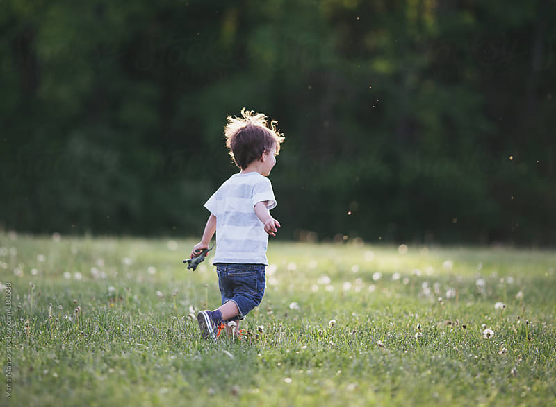 child runs through field by Maria Manco for Stocksy United
