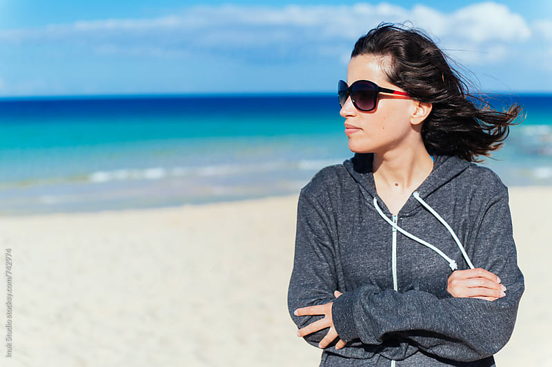 Young woman in a beach wearing sunglasses and a grey hoodie on a cold and windy day by Inuk Studio for Stocksy United