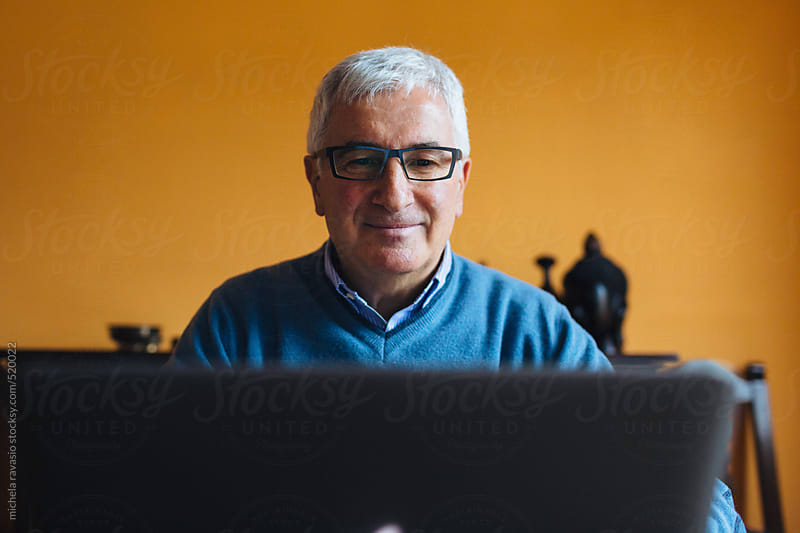 Smiling elderly man using his laptop by michela ravasio for Stocksy United