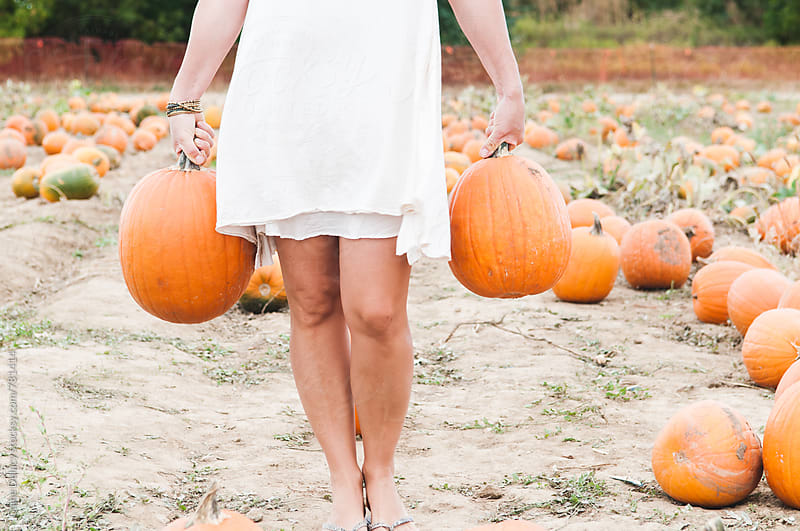 Girl in WHite dress carrying pumpkins by Caine Delacy for Stocksy United