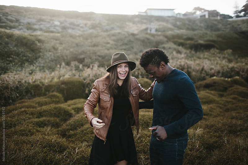 attractive couple laughing in field of dark green grass by Nicole Mason for Stocksy United