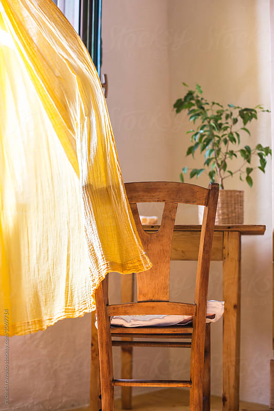 Yellow curtain waving in the room by michela ravasio for Stocksy United