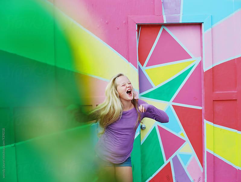 girl dancing against colorful mural fun by wendy laurel for Stocksy United