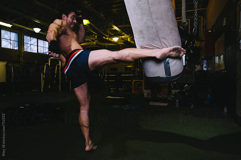 Strong man throws a powerful kick at a punching bag in a gym by Riley J.B. for Stocksy United