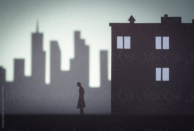 Urban scene silhouette with man detective with city buildings and skyscrapers by Cosma Andrei for Stocksy United