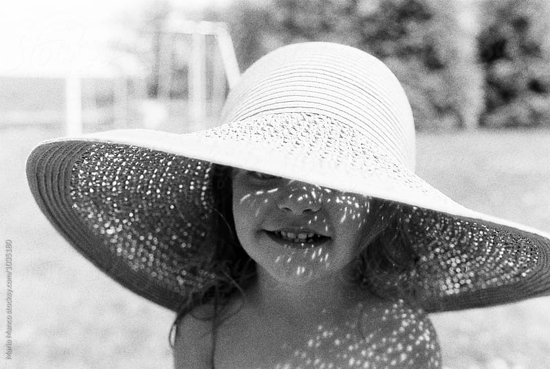 little girl in sunhat by Maria Manco for Stocksy United