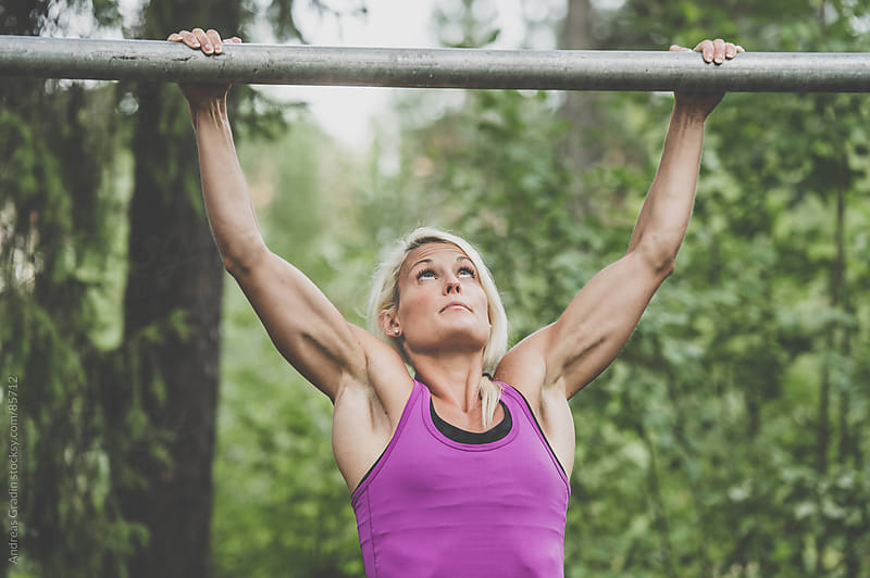 young fit woman doing pullups by Andreas Gradin for Stocksy United