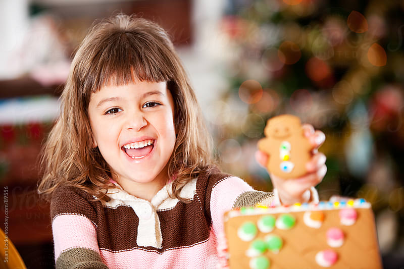 Gingerbread: Girl Laughs While Decorating House by Sean Locke for Stocksy United