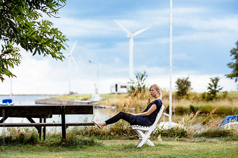Woman sitting in wooden chair at the marina by Lior + Lone for Stocksy United