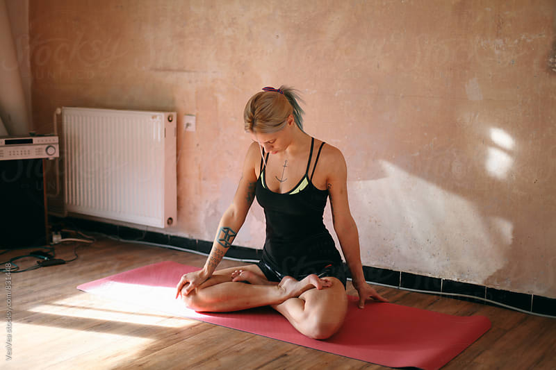 Blonde tattooed woman preparing for yoga class  by Marija Mandic for Stocksy United
