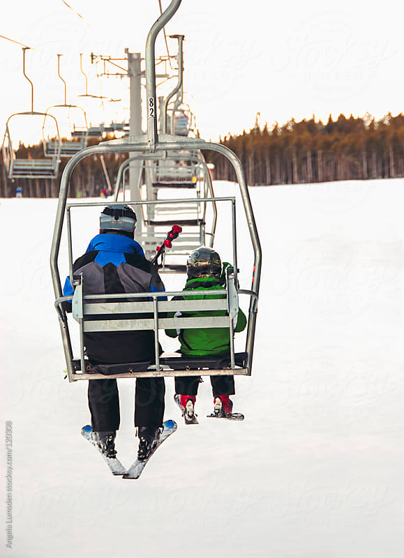Boy and his father riding a chair lift by Angela Lumsden for Stocksy United