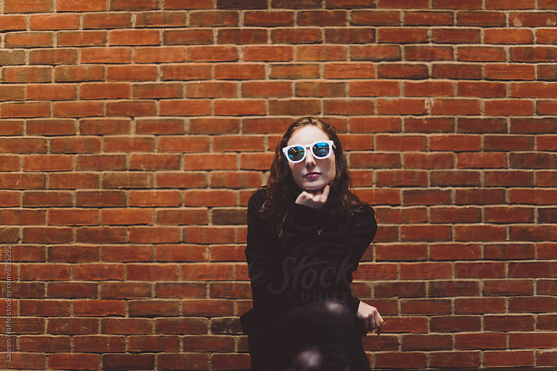 Young woman in sunglasses sitting in front of brick wall by Lauren Naefe for Stocksy United