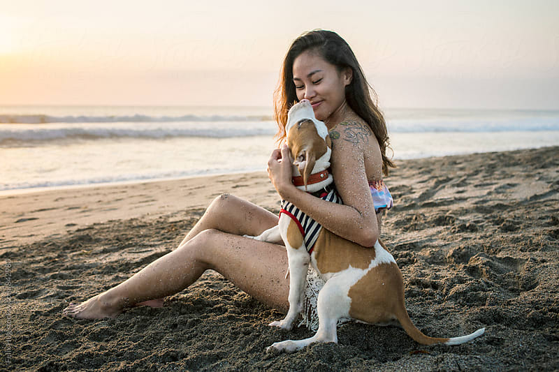 Young asian woman with her dog at beach by Felix Hug for Stocksy United