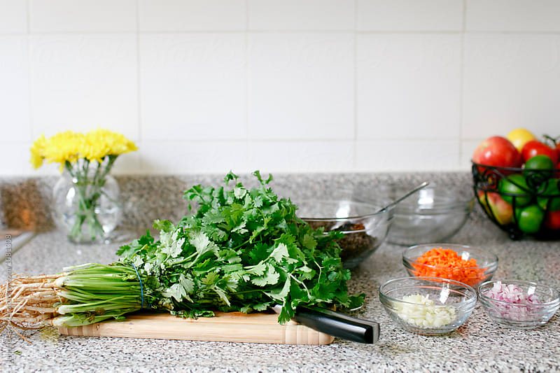 Salad ingredients lying out on countertop by Jen Brister for Stocksy United
