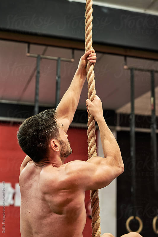 Man climbing a rope in a gym by Guille Faingold for Stocksy United