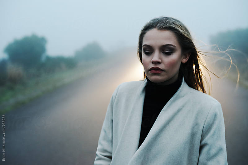 Gloomy winter's day portrait of young woman by Brent Hill for Stocksy United