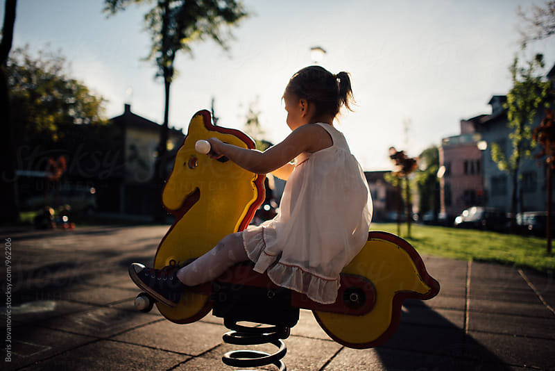 Portrait of little girl playing on a wooden toy horse  by Boris Jovanovic for Stocksy United