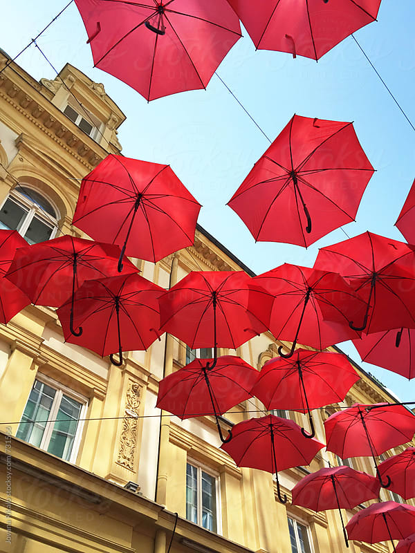 Hundreds of red umbrellas float above the street by Jovana Rikalo for Stocksy United