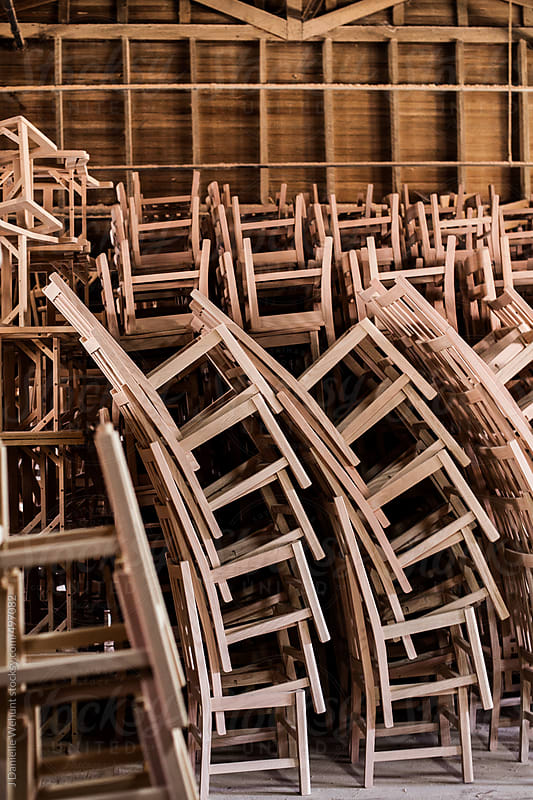 Chairs stacked to ceiling in a workshop by J Danielle Wehunt for Stocksy United