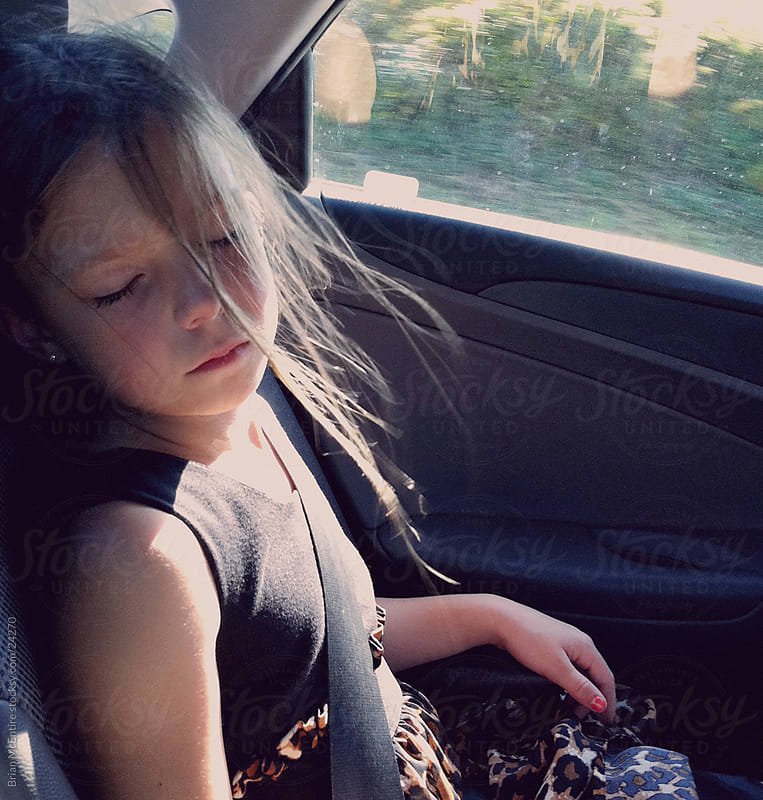 Portrait of Childhood, Girl Asleep in Car Seat by Brian McEntire for Stocksy United