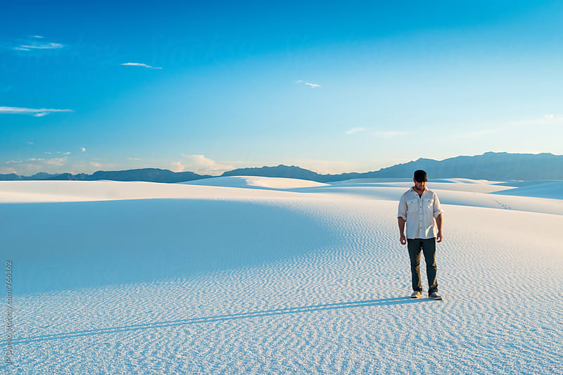 Man Walking In White Sand Dunes Vibrant Clear Blue Sky in White Sands National Monument New Mexico by JP Danko for Stocksy United