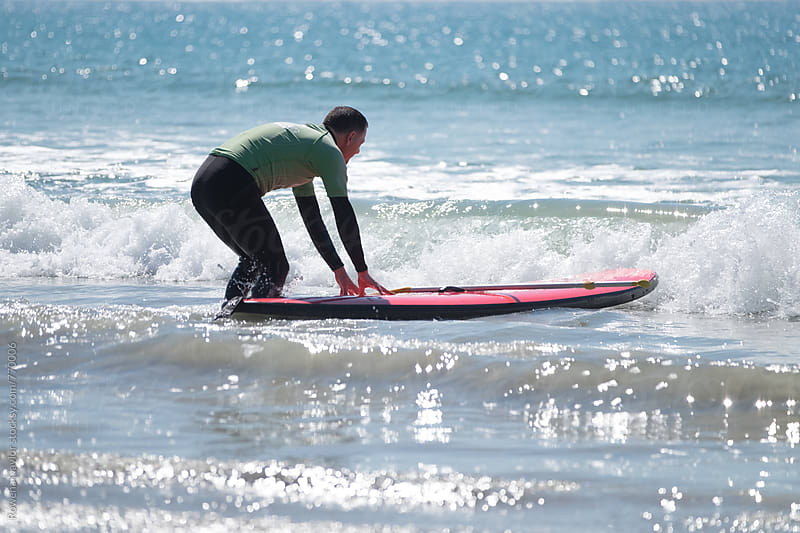 Man about to enter the ocean on a SUP by Rowena Naylor for Stocksy United