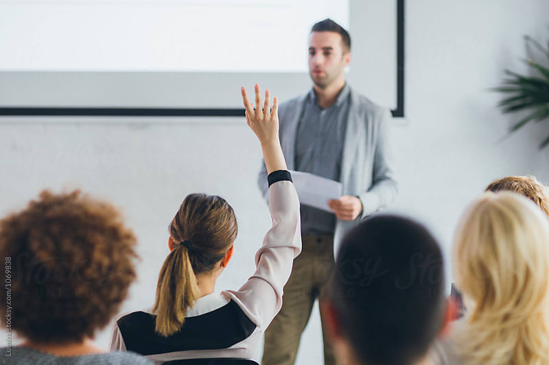 Woman Holding Her Hand Up to Ask a Question to a Lecturer. by Lumina for Stocksy United