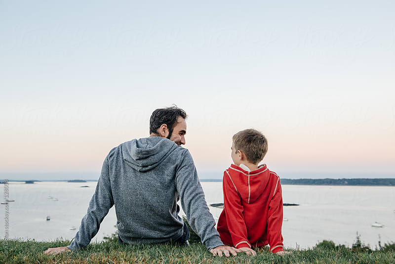 Father and son talk and laugh together as they sit on a hill overlooking the ocean by Cara Dolan for Stocksy United