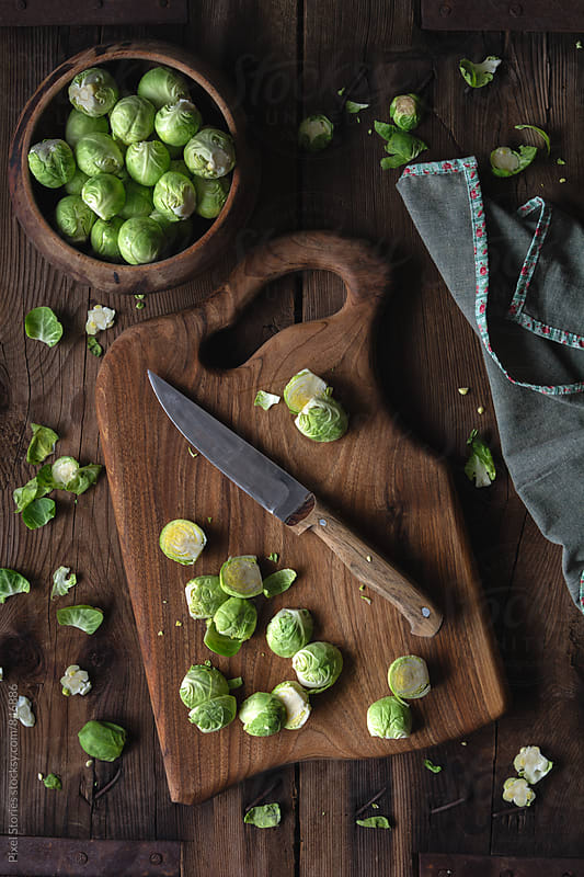 Brussels sprouts on rustic chopping board by Pixel Stories for Stocksy United