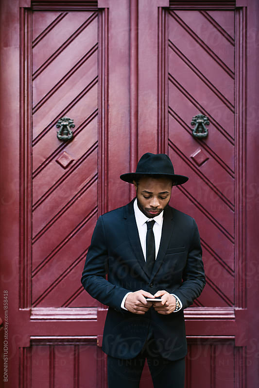 Businessman standing in front of a door using phone. by BONNINSTUDIO for Stocksy United